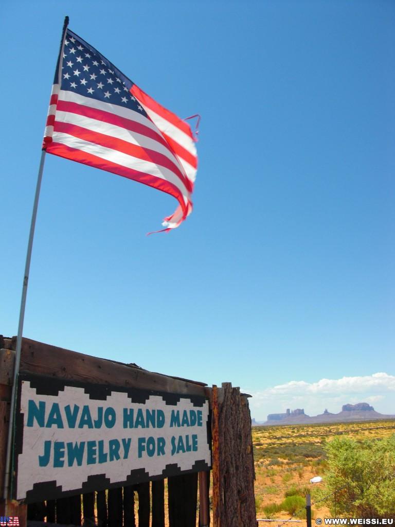 Monument Valley. Highway 163 - Monument Valley. - Fahne, Star-Spangled Banner, Monument Valley, Navajo-Nation-Reservation, Tafelberge, Landschaft, Verkaufsstand, Tribal Park, Highway 163, Stars and Stripes - (Halchita, Mexican Hat, Utah, Vereinigte Staaten)